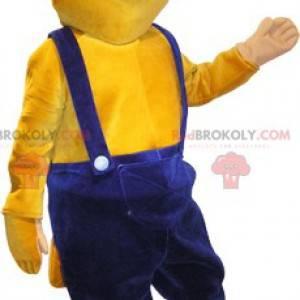 Maskottchen gelber Biber in blauen Overalls gekleidet -