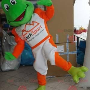 Maskotka zielona żaba ubrana w biało-pomarańczowy strój -
