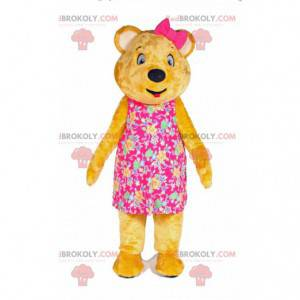 Yellow teddy bear mascot with a dress and a bow on the head -