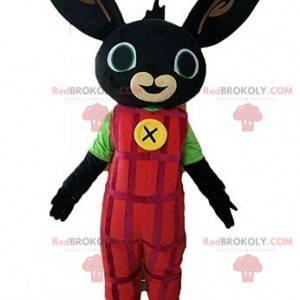 Maskotka czarny królik ubrany w czerwony kombinezon -