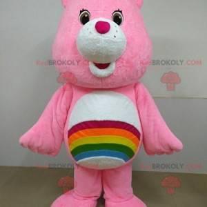 Mascotte rosa dell'orso di cura con un arcobaleno -