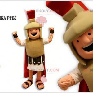 Maskotka Gladiator ubrana w beżowo-czerwony strój -