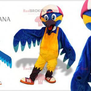 Blaues und gelbes Vogelmaskottchen mit einer Kappe -
