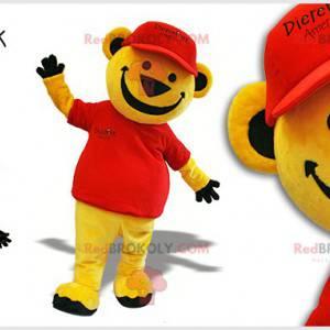 Žlutý medvěd maskot oblečený v červené barvě s víčkem -