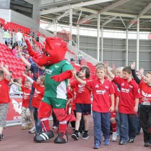 Maskot červený drak v zelené sportovní oblečení - Redbrokoly.com