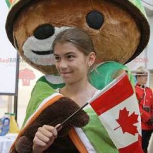 Brown bear mascot with a cape and a green helmet -